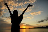 13542183-girl-raising-her-hands-during-sunset-at-the-beach